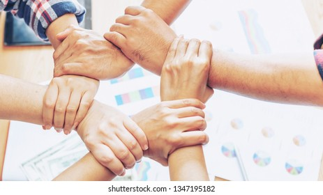 close up hand of business partnerships people crossed hands  finishing up meeting showing unity over office desk , business teamwork concept