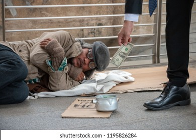 Close up hand of businessman giving money to pity beggar. Rich man donate one dollar banknote to homeless who wearing sweater, sleeping on walkway and suffering from cold weather. Sharing concept.