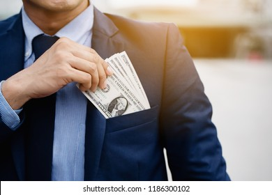 Close up hand of a businessman holding banknote into pocket. It represents very profitable investment. The exchange of currencies with good returns. And money to buy debt securities increase revenue.
