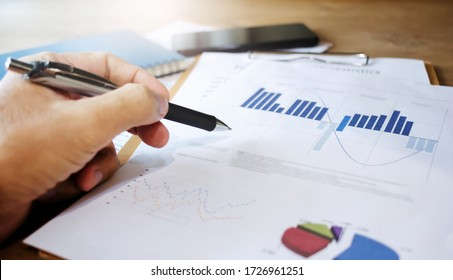 Close up hand Businessman holding pen and pointing at financial paperwork and planning  investment for business and stocks