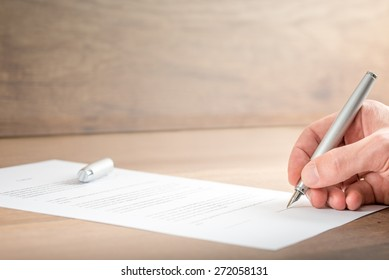 Close up Hand of a Businessman Signing a Contract Document on Top of a Wooden Table.