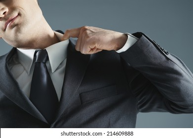 Close up of the hand of a businessman in a suit and tie easing the collar of his shirt to relieve the stress and pressure or to cool down on a hot day