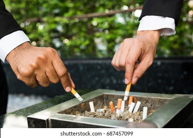 close up hand businessman two person cigarettes for smoking stand in the smoking zone area.