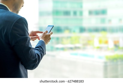 close up hand of businessman using mobile phone near office window at office building,online business concept