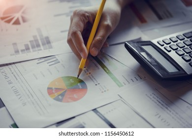 Close up hand of businesswoman or accountant working with calculator to calculate business data, and accountancy document. Business financial and accounting concept.