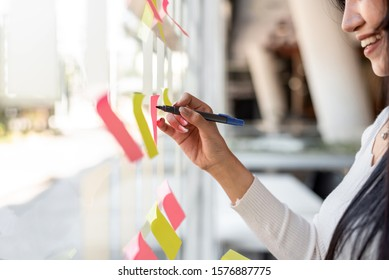 Close up hand businesswoman writing sticky notes on glass wall in office.