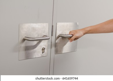 Close up hand catch at steel door handle of electric equipment room for open the door