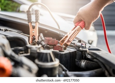 Close up of hand Charging car battery with electricity trough jumper cables