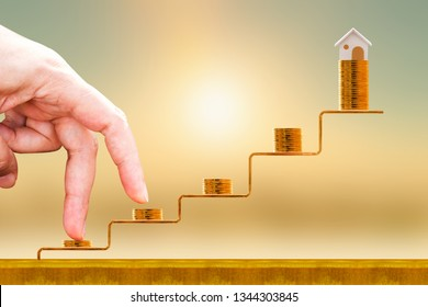 Close up of hand with climb up on a stacking five gold coin with growing on golden steps and home as destinations on sunlight background, Loan for real estate or buy a new house in the future concept.
