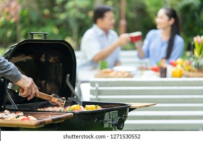 close up of hand cooking meat on barbecue for Asian couple senior or friends or family having barbecue party in nature or dinner drinking alcohol and having,meal on summer. happy moment after retire