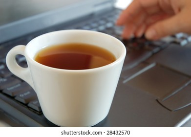 Close up of a hand and cup of coffee on laptop keyboard