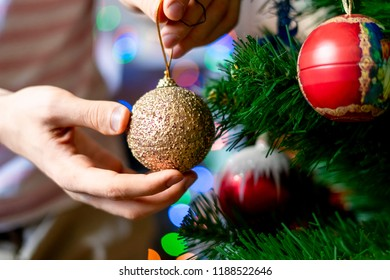 close up hand decorating the chrismas tree with beautiful red ball toy