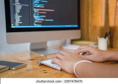 Close up hand of developing programming and coding technologies. Programmer hand typing on keyboard. Put on the wood table. Hand's Programmer concepts.