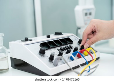 close up hand of doctor using electrical stimulator while or undergoing acupuncture treatment. Concept of Traditional Chinese Medicine. TENS (Transcutaneous Electrical Nerve Stimulation)