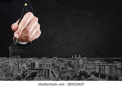 Close up of hand drawing urban city buildings
