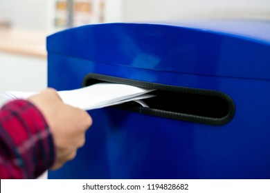 close up hand drop letter and documents in the blue postbox in post office mail