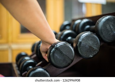 Close up hand  with dumbbells in gym concept.