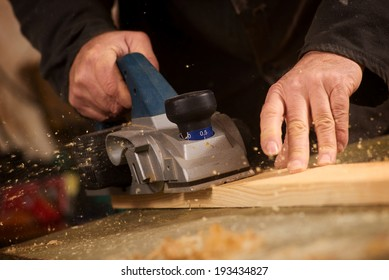 Close up of the hand of an elderly man planing a plank of wood in his carpentry workshop with a plane to smooth the surface