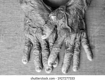 Close up of the hand of an elderly old man lay on a wooden table in BW tone