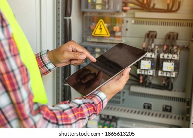 Close up hand of engineer or electrician man working check the electrical system with tablet at factory.