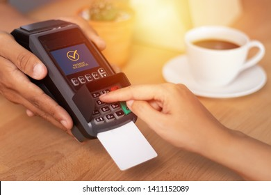 close up of hand entering credit card pin code for security password in credit card swipe machine at point of sale terminal in shop during shopping time