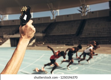 Close up of hand firing a starter pistol to start the running race. Athletes starting off for a race on a running track.
