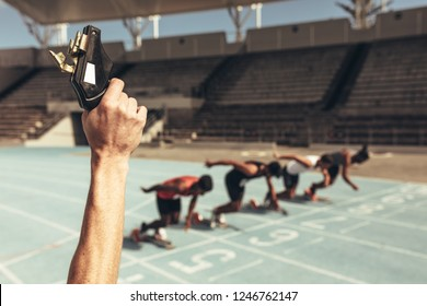 Close up of hand firing a starting pistol to start a race. Athletes taking off from starting block on a running track at the start of a race.