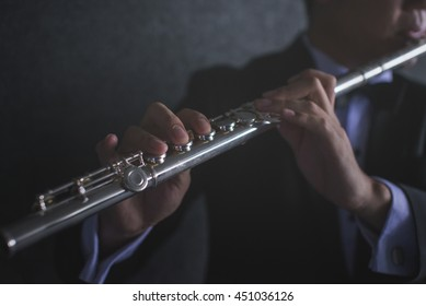 Close up hand of flutist musician performer in dark,low key image,music concept