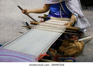 Close up hand and gold silk weaving on loom, cotton on the manual wood loom in Asian traditional culture and woman lifestyle in Thailand.