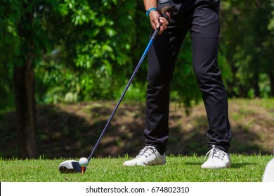 close up hand of golf player prepairing to hit the ball on tee.