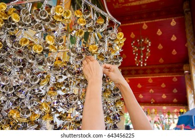 Close up : Hand grab small golden and silver bells to hanging in Thai temple. Non-English in an image is mean Wish ( in English )