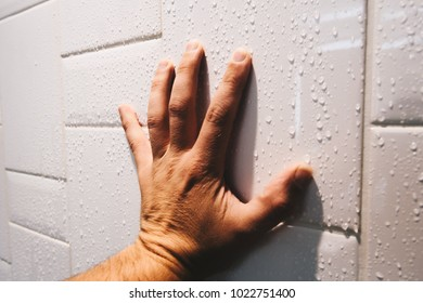 Close up of hand grasping shower tiled wall