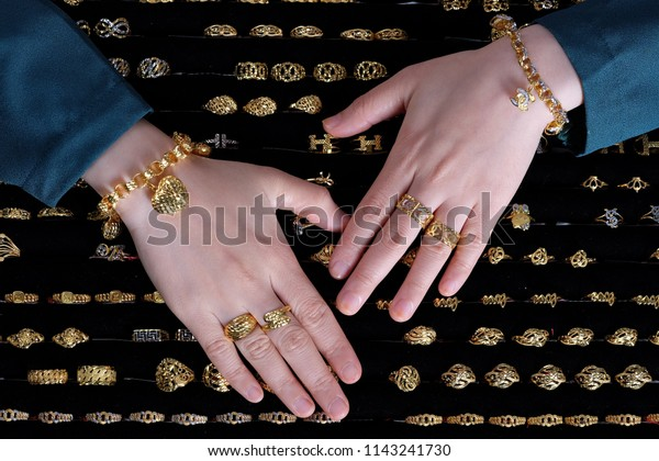 Close up hand handling jewelry tray full of gold rings