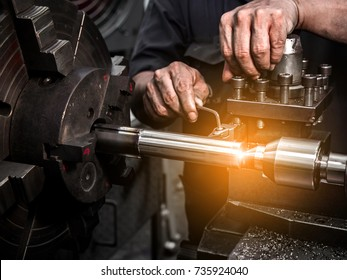 Close up hand  heavy industrial worker is working on metal work factory process by performing mechanical turning operation at machine for steel structure industry