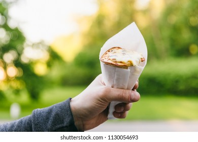 Close up hand hold pizza cone, streetfood in the green summer park