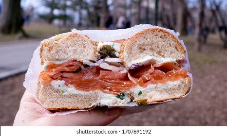 Close up of hand holding bagel with cream cheese, lox, capers, and onions outside at a park.