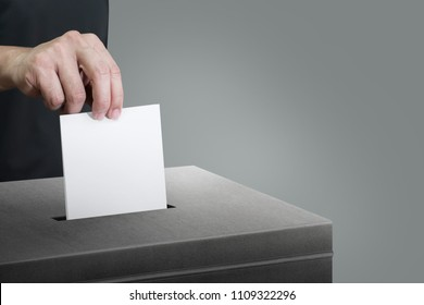 Close up of hand holding ballot at ballot box for voting concept.