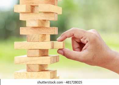 Close up hand holding blocks wood game (jenga) on blurred green background. Risk concept