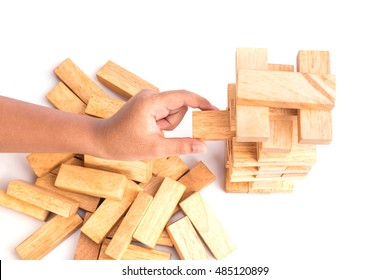 Close up hand holding blocks wood game (jenga) isolated on white background. Risk concept