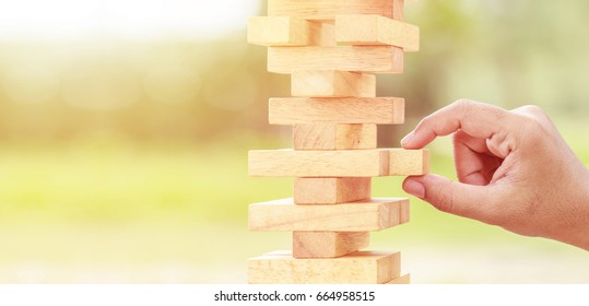 Close up hand holding blocks wood game on blurred green background. With copy space for text or design concept