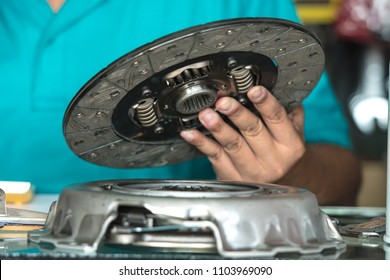 Close up of hand holding a clutch disc in the automotive spare parts store.
