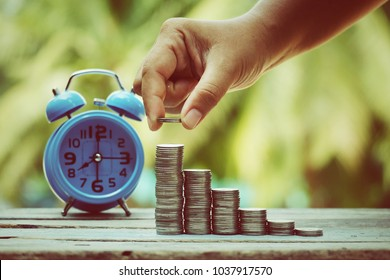 close up hand holding coin, stack of money and blue alarm clock on old wood table, saving money for future, manage time for success business concept, vintage tone