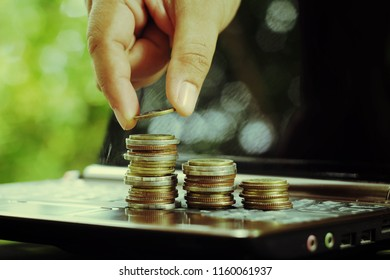 close up hand holding coin, stack of money on notebook, saving money for future, manage to success, shopping online business technology concept, vintage tone