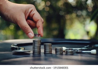close up hand holding coin, stack of money and stethoscope on table, saving and manage for healthcare business, life insurance technology, economic crisis risk and problem concept
