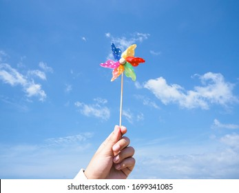 Close up hand holding colorful pinwheel over blue sky background. Children`s colorful wind turbine toy.