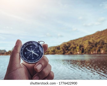 close up hand holding compass with moutain and river background, travel bubble and relaxation lifestyle, plan and manage to success business concept