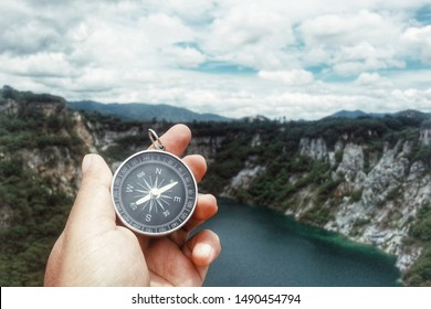 close up hand holding compass, nature background, Grand canyon, Chonburi, Thailand, travel and lifestyle concept