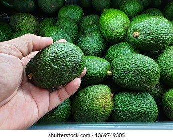 Close up hand holding fresh Avocado in grocery store