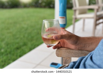 Close up of a hand holding a glass of rose outside on a summer day