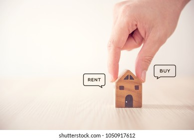 Close up Hand holding home with Buy or Rent, copy space.